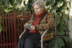 Escritura mayor de la mujer en el sillón de ruedas - horizontal Imagenes de archivo