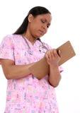 Escritura pediátrica hermosa de la enfermera en el sujetapapeles Imagen de archivo