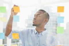 Escritura pensativa del hombre de negocios en notas pegajosas sobre ventana Imagen de archivo libre de regalías