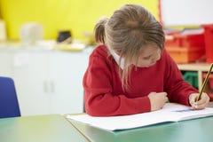 Escritura practicante del alumno femenino en la tabla Imagen de archivo