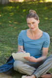 Escritura relajada de la mujer joven en el tablero en el parque Foto de archivo