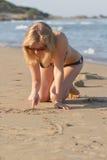 Escritura rubia de la muchacha en la arena Fotos de archivo libres de regalías