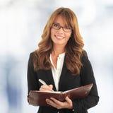 Escritura de la mujer de negocios en su cuaderno Foto de archivo libre de regalías