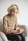 Escritura rubia de la mujer joven en su diario Foto de archivo libre de regalías