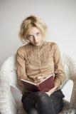 Escritura rubia de la mujer joven en su diario Imagen de archivo libre de regalías