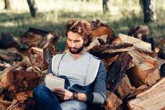 Escritura seria del hombre en cuaderno en la pila de madera Imagen de archivo libre de regalías