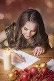 Escritura sonriente de la muchacha en la decoración de la Navidad foto de archivo libre de regalías