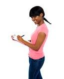 Escritura sonriente de la muchacha en el sujetapapeles Fotos de archivo