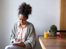 Escritura sonriente de la mujer en el cuaderno de notas en casa Fotografía de archivo