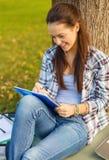 Escritura sonriente del adolescente en cuaderno Fotografía de archivo libre de regalías