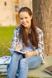 Escritura sonriente del adolescente en cuaderno Fotos de archivo libres de regalías