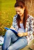 Escritura sonriente del adolescente en cuaderno Foto de archivo libre de regalías