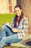 Escritura sonriente del adolescente en cuaderno Fotografía de archivo