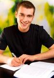 Escritura sonriente joven del hombre Foto de archivo libre de regalías