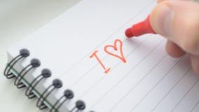 Escritura TE AMO de U con el marcador rojo en libreta metrajes