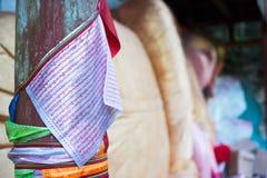 Escritura tibetana en las banderas que cuelgan cerca de un Buda de mentira en Gaomiao t Fotos de archivo
