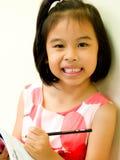 Escritura y lectura de la chica joven fotografía de archivo