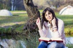Escritura y lectura de la mujer joven que un libro en un otoño parquea Imagen de archivo