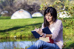 Escritura y lectura de la mujer joven que un libro en un otoño parquea Imágenes de archivo libres de regalías