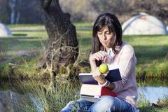 Escritura y lectura de la mujer joven que un libro en un otoño parquea Foto de archivo libre de regalías
