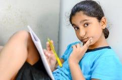 Escritura y lectura del niño de la niña que miran la cámara foto de archivo libre de regalías