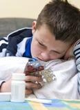 Escrituras de la etiqueta de las píldoras de la lectura del muchacho Fotografía de archivo libre de regalías