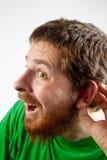 Escucha - el hombre curioso divertido con la mano en el oído imágenes de archivo libres de regalías