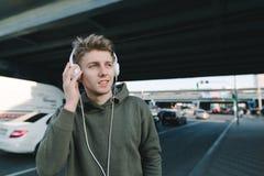 Escuchado la música por el hombre en los auriculares contra el contexto del paisaje urbano, de los caminos y de los coches Forma  Imagen de archivo libre de regalías