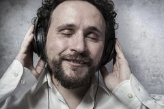Escuchando y disfrutando de la música con los auriculares, hombre en la camisa blanca Fotos de archivo