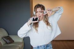 Escuche la música, cante en el teléfono como el micrófono Retrato de la mujer joven feliz en casa Imagen de archivo libre de regalías