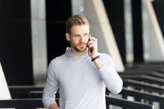 Escuche mí La barba del hombre camina con el smartphone, fondo urbano Hombre con smartphone serio de la charla de la cara de la b foto de archivo libre de regalías