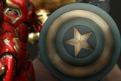 Escudo ascendente cercano del tiro de la figura de los superheros de capitán America en la acción que aparece en cómic americanos foto de archivo libre de regalías