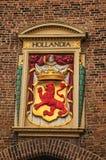 Escudo de armas colorido y de oro de los derechos que adornan la pared de ladrillo en La Haya Imagen de archivo libre de regalías