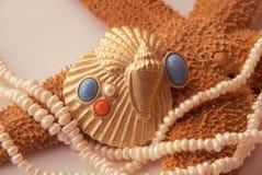 Escudo dourado com pérola, turquesa, coral, starfis Imagens de Stock Royalty Free