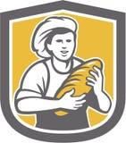 Escudo femenino de Holding Bread Loaf del panadero Foto de archivo