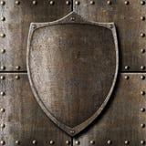 Escudo viejo del metal sobre fondo de la armadura Imagen de archivo