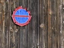 Escudo viejo erosionado del estacionamiento prohibido en una pared de madera antigua Imagen de archivo