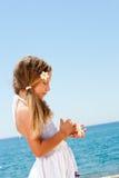 Escudos bonitos da terra arrendada da menina na praia ensolarada. fotografia de stock