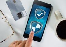 Escudos de la protección de seguridad del antivirus tocados en el teléfono fotos de archivo