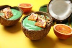 Escudos do coco com o batido saboroso e as laranjas do spirulina no fundo da cor fotografia de stock royalty free