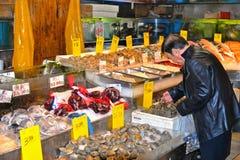 Escudos dos moluscos da compra do homem no mercado de peixes de pouca loja da porcelana em Manhattan, New York foto de stock