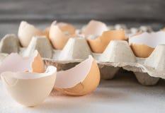 Escudos quebrados dos ovos da galinha em um fundo branco fotos de stock royalty free