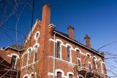 Escuela abandonada, histórica con el ladrillo rojo y dinteles blancos de la piedra caliza Foto de archivo