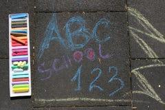 Escuela, ABC y suspiro 123 escritos con tizas coloreadas en un pavimento Dibujo de nuevo a escuela en un asfalto y concepto de la Imágenes de archivo libres de regalías