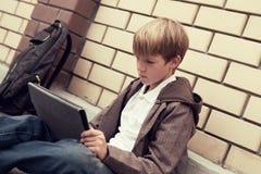 Escuela adolescente con la sentada electrónica de la tablilla Fotos de archivo libres de regalías