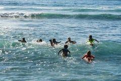 Escuela de la resaca - varios estudiantes surfboarding dirigieron en un océano Imagenes de archivo