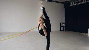 Escuela gimnástica y energía Gimnasta de la muchacha en ropa de deportes negra con la cuerda en fractura Flexibilidad en la acrob almacen de video