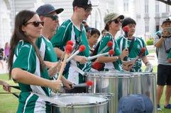 Escuela internacional Samba Drummers de SJI en el día de St Patrick en Singapur foto de archivo