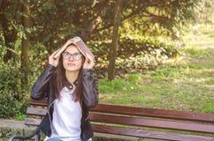 Escuela o estudiante universitaria hermosa joven con los vidrios que se sientan en el banco en el parque que lee los libros y el  Imagen de archivo libre de regalías