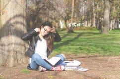Escuela o estudiante universitaria joven hermosa con el pelo largo, los vidrios y la chaqueta de cuero negra sentándose en la tie Imagenes de archivo